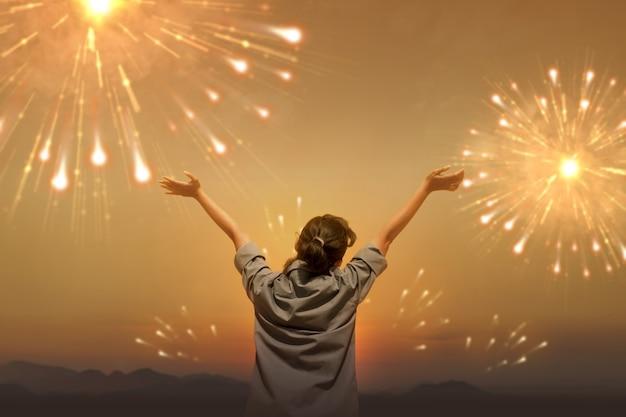 Vista traseira de uma mulher asiática com uma expressão feliz, comemorando o ano novo com fogos de artifício no céu. feliz ano novo 2021