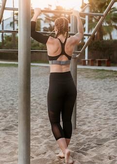 Vista traseira de uma mulher atlética na praia fazendo exercícios de fitness