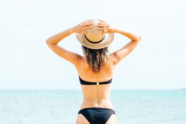 Vista traseira de uma mulher bonita posando de biquíni preto