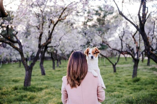 Vista traseira de uma mulher caucasiana e um cachorro no parque na primavera ao pôr do sol. conceito de amor e amizade. animais de estimação ao ar livre