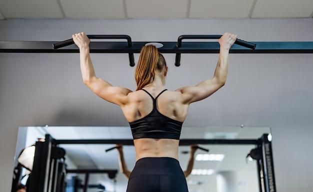 Vista traseira de uma mulher com cabelo no rabo de cavalo, fazendo exercícios de aperto na barra no ginásio.