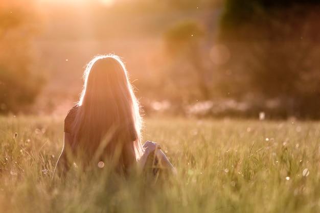Vista traseira de uma mulher com cabelos longos, sentado ao ar livre na luz do sol, curtindo a natureza.