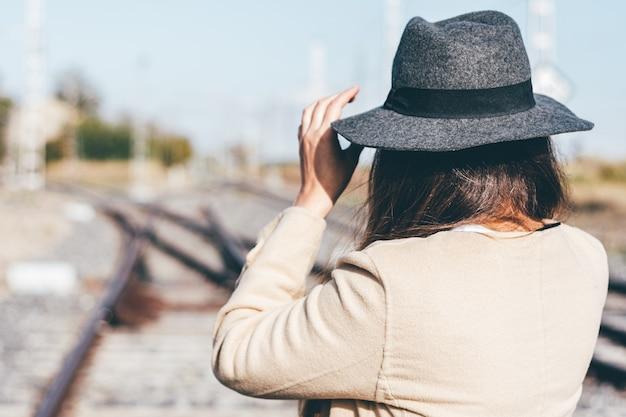 Vista traseira de uma mulher com capa de chuva bege e chapéu na ferrovia abandonada.