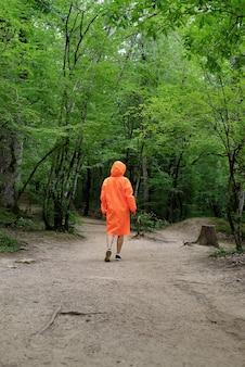 Vista traseira de uma mulher com capa de chuva laranja, caminhando na floresta. estilo de vida ativo e viagens