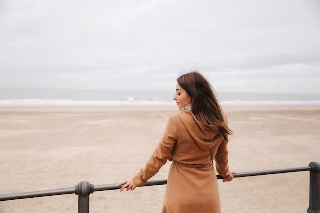 Vista traseira de uma mulher com casaco marrom em pé ao longo do mar do norte, olhando para as ondas