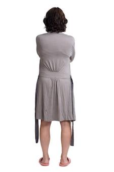 Vista traseira de uma mulher com roupão em fundo branco, mãos no quadril