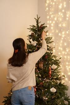 Vista traseira de uma mulher com roupas casuais com laço vermelho no cabelo castanho, decorando a árvore de natal