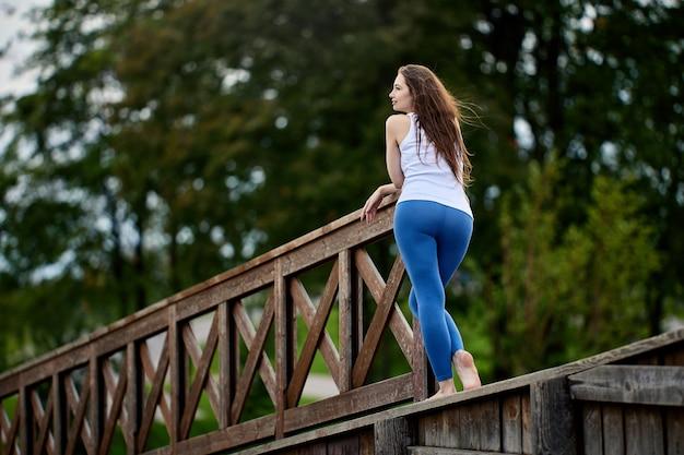 Vista traseira de uma mulher com uma bela figura de pé em um elemento de madeira do paisagismo em um parque público