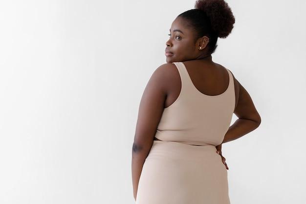 Vista traseira de uma mulher confiante posando enquanto usava um modelador de corpo