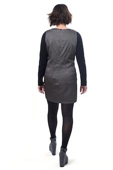 Vista traseira de uma mulher de meia-idade com um vestido em fundo branco, andando em branco