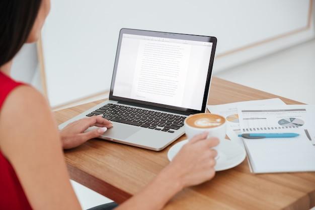 Vista traseira de uma mulher de negócios de camisa vermelha sentada no local de trabalho com laptop, xícara de café e documentos