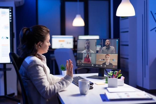 Vista traseira de uma mulher de negócios falando sobre o relatório de venda em videoconferência fazendo hora extra no escritório de start-up