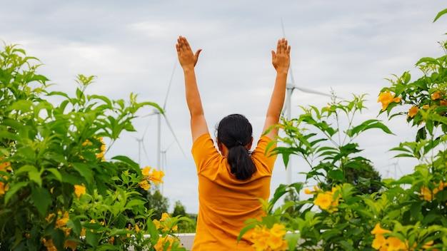 Vista traseira de uma mulher despreocupada com os braços estendidos em campo com moinhos de vento em um dia frio