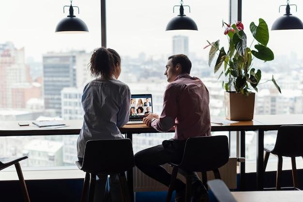 Vista traseira de uma mulher e um homem no escritório fazendo uma videochamada