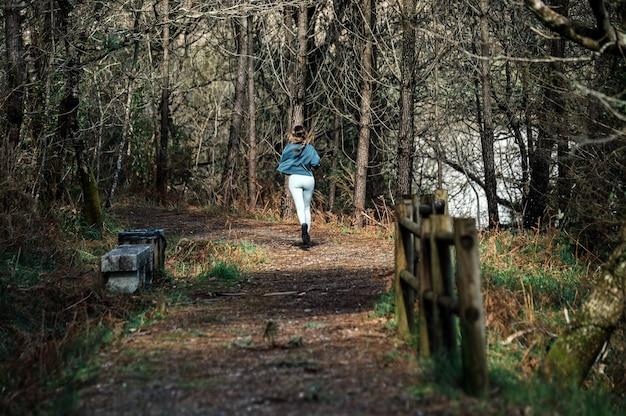 Vista traseira de uma mulher em forma irreconhecível, vestindo roupas esportivas, correndo ao longo da trilha na floresta