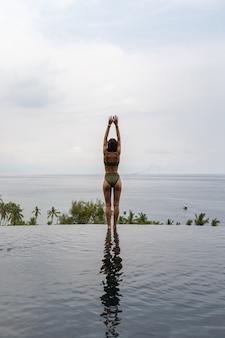 Vista traseira de uma mulher em pé com a profundidade do tornozelo em uma piscina em uma ilha exótica