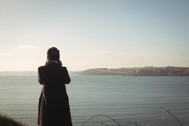 Vista traseira de uma mulher em pé perto do lago no parque