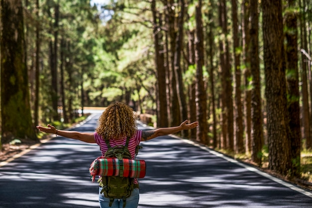 Vista traseira de uma mulher encaracolada abrindo os braços e curtindo a viagem pela estrada com uma mochila - estilo de vida de liberdade de pessoas alternativas caminhando na estrada no meio de uma floresta de árvores altas