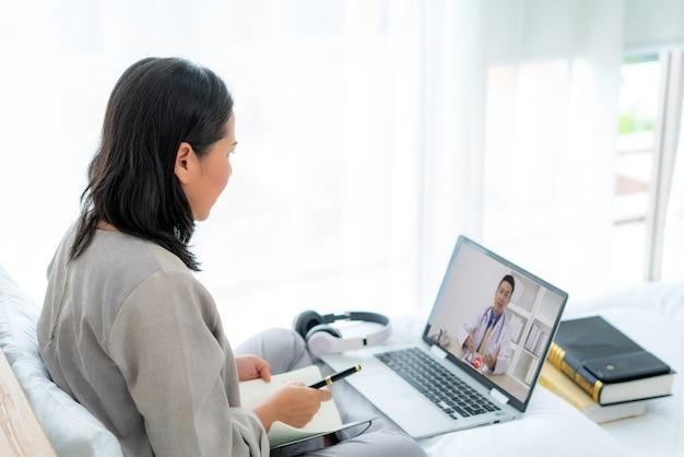 Vista traseira de uma mulher fazendo videochamada com o médico e sentindo-se doente