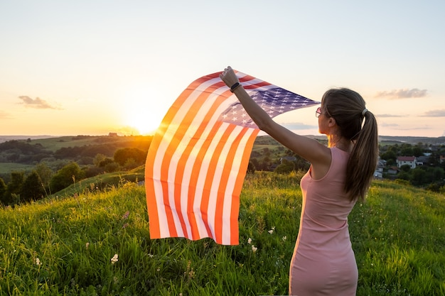 Vista traseira de uma mulher feliz com a bandeira nacional dos eua em pé ao ar livre ao pôr do sol. mulher positiva comemorando o dia da independência dos estados unidos. dia internacional do conceito de democracia.