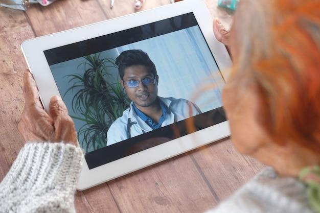 Vista traseira de uma mulher idosa em consulta online com um médico em um tablet digital