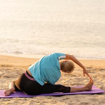 Vista traseira de uma mulher idosa se alongando na praia