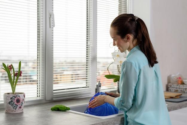 Vista traseira de uma mulher lavando pratos na cozinha em frente à janela