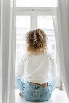 Vista traseira de uma mulher loira de cabelos cacheados relaxando em casa