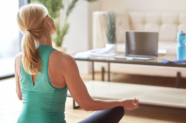 Vista traseira de uma mulher loira madura sentada em posição de lótus no chão e assistindo online