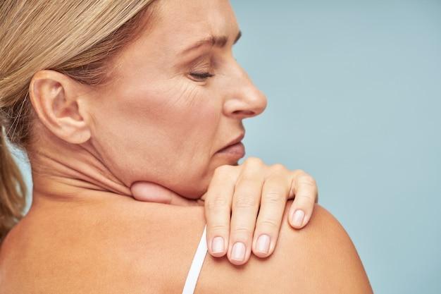 Vista traseira de uma mulher madura tocando seu ombro com a pele macia em pé contra o azul