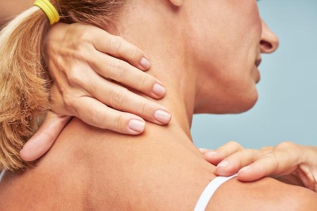 Vista traseira de uma mulher madura tocando seu pescoço e ombro em pé contra um fundo azul
