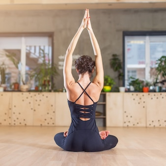 Vista traseira de uma mulher magra fazendo exercícios de ioga, meditando sentada em posição de lótus com os braços levantados