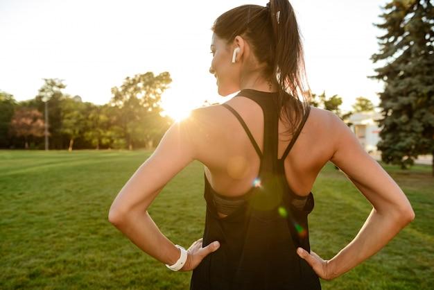 Vista traseira de uma mulher magro fitness em fones de ouvido