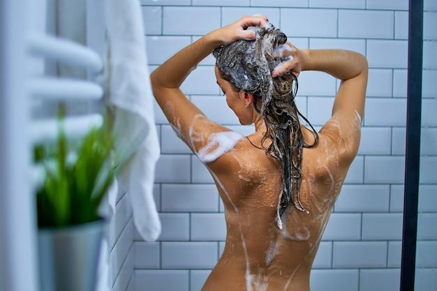 Vista traseira de uma mulher nua lavando o cabelo com shampoo enquanto toma banho