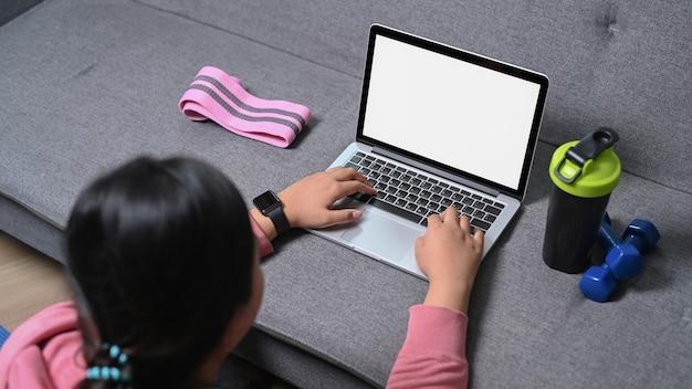 Vista traseira de uma mulher obesa assistindo o treinamento on-line no laptop em casa.