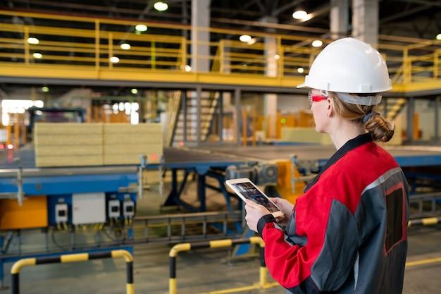 Vista traseira de uma mulher ocupada com capacete de segurança e óculos de segurança usando tablet enquanto controla o processo da linha de produção na fábrica