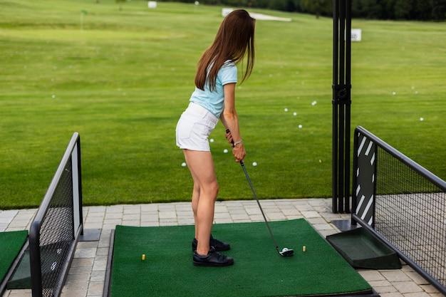Vista traseira de uma mulher praticando golfe