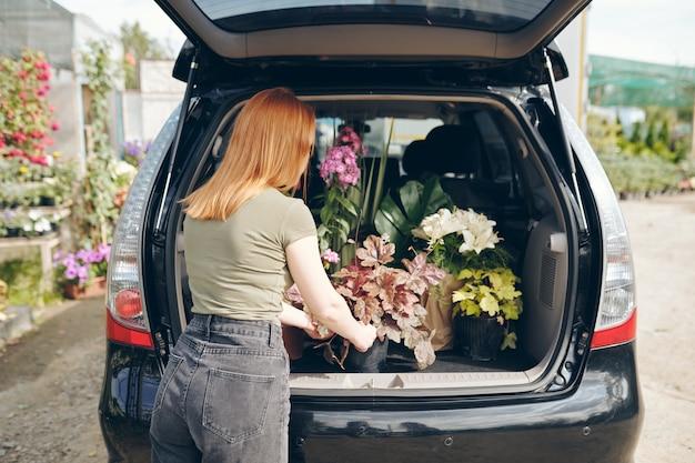 Vista traseira de uma mulher ruiva de camiseta e calça jeans parada perto do porta-malas e carregando flores no carro depois de fazer compras no mercado de flores