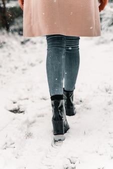 Vista traseira de uma mulher sem rosto com um casaco quente caminhando ao longo de uma trilha de neve na floresta em um dia de inverno