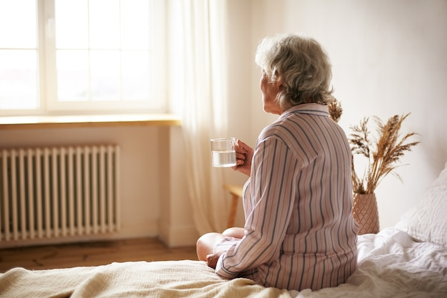 Vista traseira de uma mulher sênior de sessenta anos de idade com cabelos grisalhos, segurando uma caneca para lavar o remédio para dormir, sofrendo de insônia. idosa aposentada tomando remédio com água, sentada no quarto