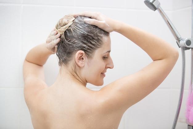 Vista traseira de uma mulher sexy lavando o cabelo com shampoo no banho