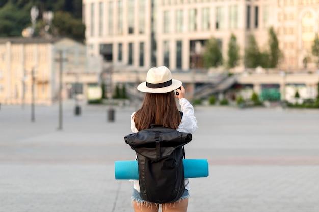 Vista traseira de uma mulher tirando fotos enquanto viaja com a mochila