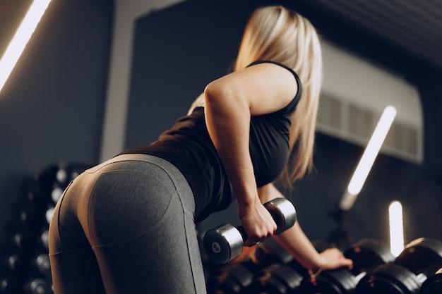 Vista traseira de uma mulher treinando as mãos com um haltere em uma academia