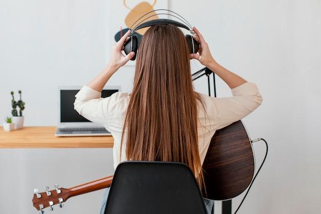 Vista traseira de uma musicista com violão e fones de ouvido