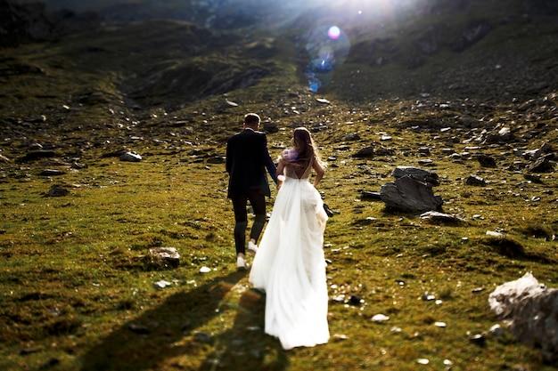 Vista traseira de uma noiva e um noivo irreconhecível correndo nas montanhas de mãos dadas contra o nascer do sol.
