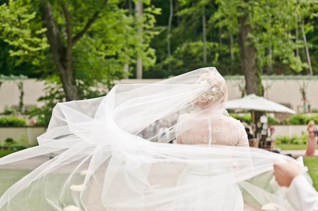 Vista traseira de uma noiva em um vestido de renda com um véu tremulando ao vento é enviado para o local da cerimônia de casamento