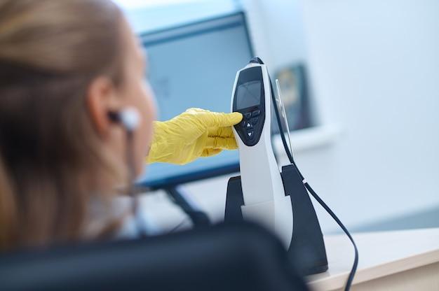 Vista traseira de uma paciente sentada durante o teste de audiometria realizado por um médico certificado