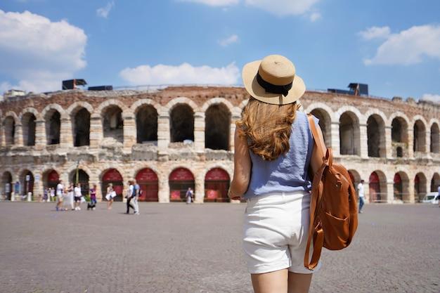 Vista traseira de uma turista caminhando em direção à arena de verona, itália