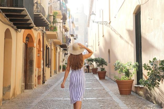 Vista traseira de uma turista caminhando na cidade velha de cefalu, na sicília, itália