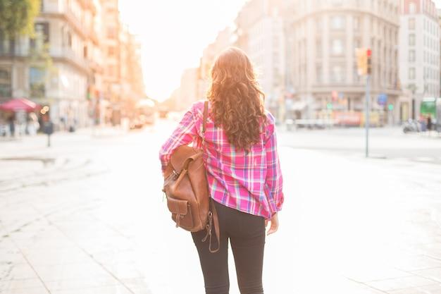 Vista traseira de uma turista com uma mochila caminhando pela rua e viajando sozinha. mulher de cabelos curtos olhando ao redor e desfrutando arquitetura da cidade. viajando no conceito de fim de semana